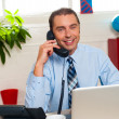 Smiling manager in middle of business interactions — Stock Photo