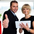 Secretary with a tablet posing with her successful boss — Stock Photo