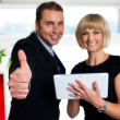 Secretary with a tablet posing with her successful boss — Stock Photo #19566537