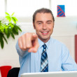 Businessman at work desk pointing at you — Stock Photo