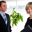 Handsome boss passing by smiling female colleague — Stock Photo
