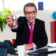 Stock Photo: Happy male executive handing over keys