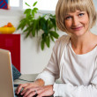 Blonde woman facing camera while working on laptop — Stock Photo #19566833