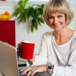 Cheerful woman holding coffee mug and working - 图库照片