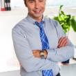 Young manager in formals standing with arms crossed — Stock Photo
