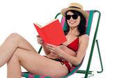 Enticing bikini model on a deckchair reading a book — Stock Photo
