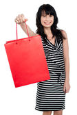 Smiling woman offering bag full of gifts — Stock Photo