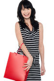 Joyous brunette posing with red shopping bag — Stock Photo