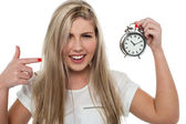 Girl pointing towards old fashioned time piece — Stock Photo