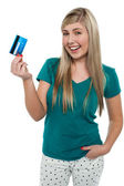 Joyous teenager displaying credit card — Stock Photo