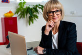 Thoughtful business lady seated in office — Stock Photo