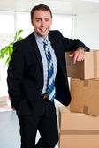 Executive with his hand placed on pile of cardboard cartons — Stock Photo