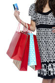Stylish woman walking with shopping bags and credit card — Stock Photo