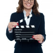 Gorgeous corporate woman holding a clapperboard — Stock Photo #19571497
