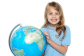 Pretty school child holding globe and pointing — Stock Photo