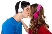 Young couple enjoying music and kissing — Stock Photo
