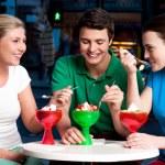 Three friends enjoying tempting dessert — Stock Photo #24586021