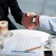 Business handshake over a coffee — Stock Photo #24589883