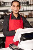 Cheerful barista staff at the cash counter — Stock Photo