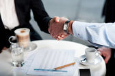 Business handshake over a coffee — Stock Photo
