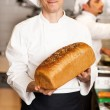 Chef showing freshly baked whole grain bread — Stock Photo #24591763