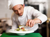A chef arranging tossed salad in a white bowl — Stock Photo