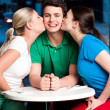 Two girls kissing handsome young boy — Stock Photo