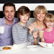 Family enjoying breakfast at a restaurant - Stok fotoğraf