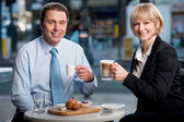 Two corporates discussing business over snacks — Stock Photo