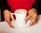 Hands of waiter serving a cup of cappucino — Stock Photo