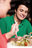 Handsome young guy enjoying meal in restaurant — Stock Photo