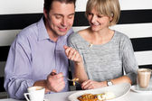 Couple rejoicing their meal in food court — Stock Photo