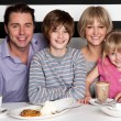 Family of four having great time in restaurant — Stock Photo #24624901