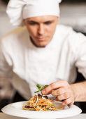 шеф-повар, украшая салат макароны с травяные листья — Стоковое фото