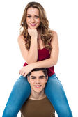 Pretty girl sitting on the shoulders of her boyfriend — Stock Photo