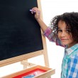 Beautiful little girl writing on classroom board — Stock Photo #25304111