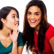 Two young girls gossiping - Stockfoto