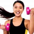 Happy fitness woman lifting dumbbells — Stock Photo
