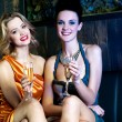 Pretty sensual girls in a nightclub, relishing wine — Stock Photo