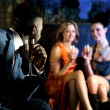 Elegant man looking at hot young girls in nightclub — Stock Photo #25306325