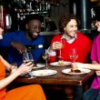 Four friends enjoying dinner at a restaurant — Stock Photo #25306579