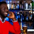 Smiling young guy in bar looking at something — Stock Photo