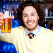 Royalty-Free Stock Photo: Happy man offering glass of beer, let\'s celebrate