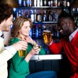 Постер, плакат: Group of three friends in a bar drinking beer