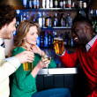 Group of three friends in a bar drinking beer — Stock Photo