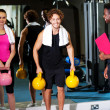 Happy man and woman lifting kettlebell — Stok fotoğraf
