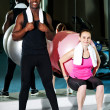 Man and woman exercising in gym - Stock Photo