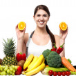 Stock Photo: Attractive fit smiling girl holding fresh sliced oranges