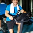 Fitness man riding a static bike inside gym — Stock Photo