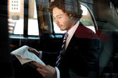 Man reading newspaper inside taxi cab — Stock Photo